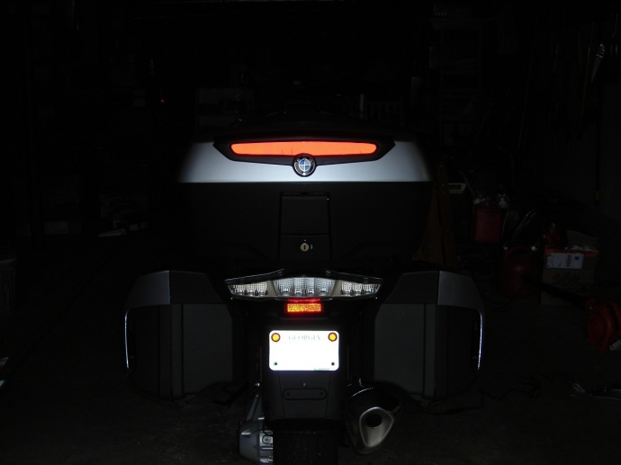 The back end of the motorcycle and high, red reflector with flash.